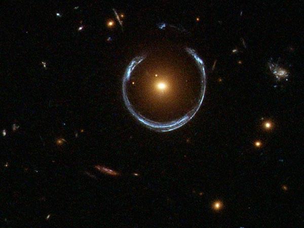 Kính thiên văn vũ trụ Hubble cho thấy hình ảnh một thiên hà khổng lồ màu đỏ được bao quanh bởi vòng hào quang màu xanh.