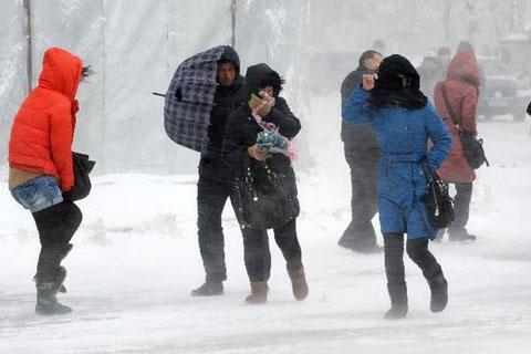 Người dân gồng mình chống chọi với gió và tuyết trên đường phố Thẩm Dương.
