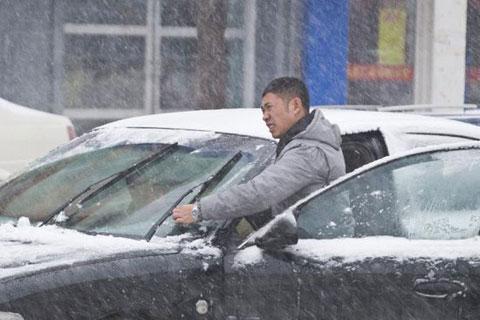 Một người lái xe gạt tuyết để mở rộng tầm nhìn trên đường phố của tỉnh Cát Lâm, miền đông bắc Trung Quốc.