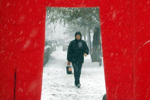 Một người đội mưa tuyết đến nơi làm việc ở Cát Lâm.