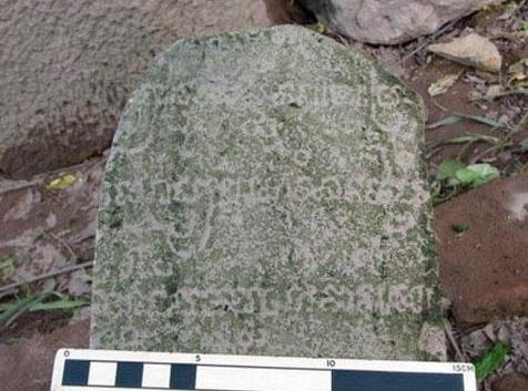 Một phiến đá hình trụ trên thân được khắc chạm nhiều chữ cổ nằm sâu dưới  lòng đất được các nhà khảo cổ phát lộ dưới lòng đất khu đến tháp Mỹ Sơn.