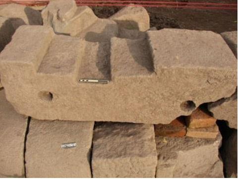 Một phiến đá dài có lỗ mộng sâu được xác định là đà cửa đền thờ