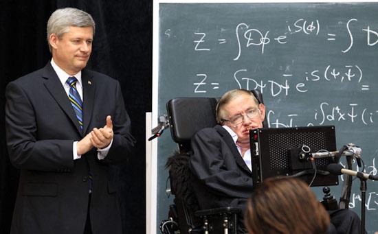 Thủ tướng Canada Stephen Harper vỗ tay phía sau nhà vật lý học Stephen Hawking