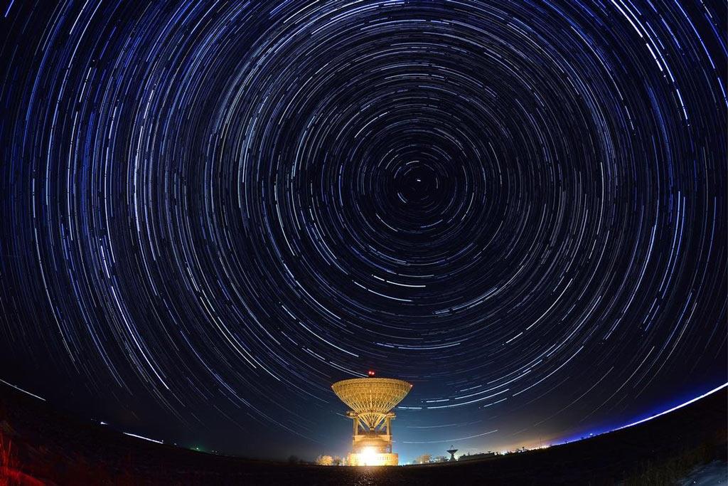 Xoay cùng màn đêm. Một chiếc máy ảnh thực hiện chụp phơi sáng cực lâu ở Trung tâm Thử nghiệm Không gian Titov vùng viễn đông của Nga. Những vòng sáng trên bầu trời là hướng di chuyển của những ngôi sao (không phải sao băng) tạo ra.