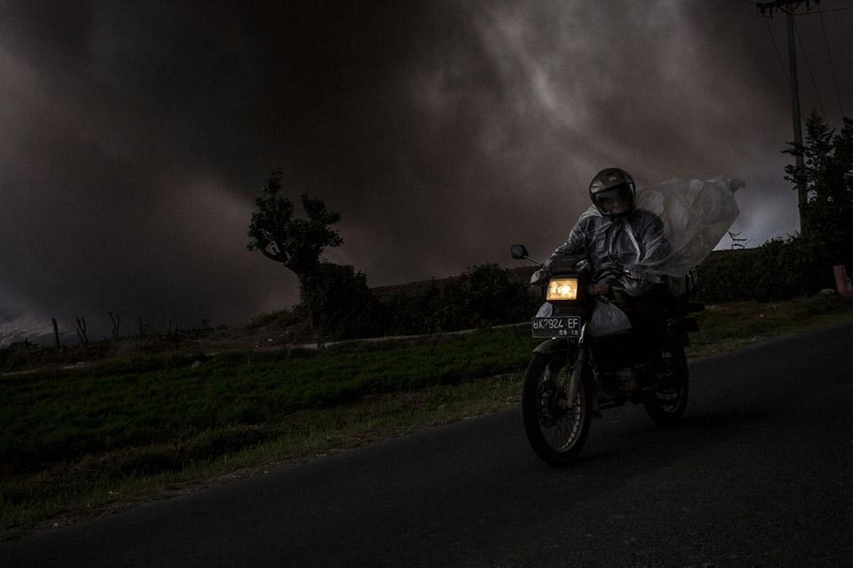Người đàn ông trên chiếc xe máy khi núi Sinabung phun tro, nhìn từ làng Tiga Kicat ngày 20 tháng 06 năm 2015