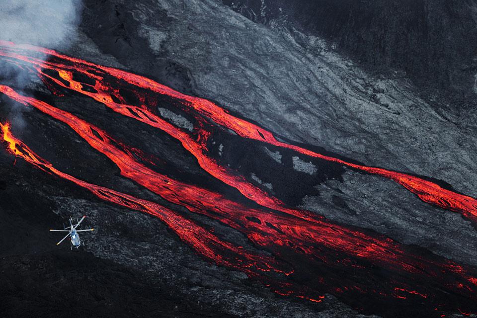 Một chiếc trực thăng bay bên trên những dòng dung nham chảy ra khỏi nuis lửa Piton de la Fournaise núi khi nó phun trào vào ngày 17 tháng 05 năm 2015, trên hòn đảo của Pháp thuộc Réunion Island ở Ấn Độ Dương.