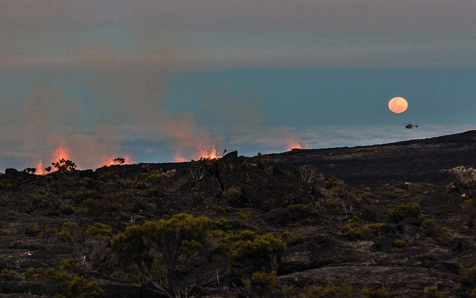Mặt trăng bắt đầu mọc khi dung nham nóng chảy được phun ra từ núi Piton de la Fournaise, một trong những núi lửa hoạt động mạnh nhất trên thế giới, ngày 31 tháng 07 năm 2015, trên đảo Reunion.