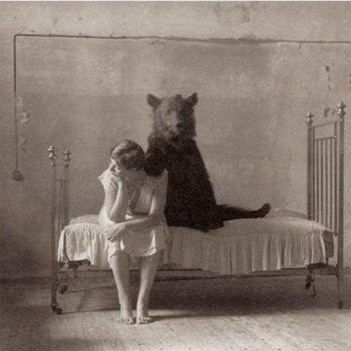 """Trong ảnh là một người phụ nữ đang ngồi trên giường bệnh và cô dường như không hề biết đến sự tồn tại của một con """"ma gấu"""" đang mỉm cười đầy nguy hiểm ngay trên giường mình."""