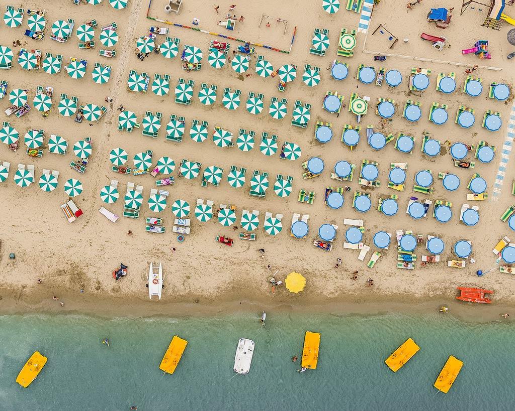 Những chiếc ô màu sắc tương phản với bãi cát vàng và biển xanh trên bờ biển Adriatic, vào một ngày mùa hè sôi động trong ảnh của Bernhard Lang.