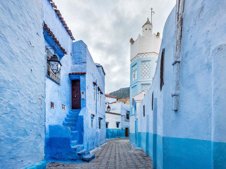 """Nằm cheo leo trên dãy núi Rif ở Morocco, thị trấn màu xanh nước biển Chefchaouen mang một vẻ đẹp yên bình. Những người Do Thái tị nạn từ châu Âu lần đầu sơn thị trấn vào những năm 1930. Có ý kiến cho rằng màu xanh để biểu tượng cho thiên đường, lại có người nói đó là để tránh muỗi. Vì lẽ đó, thị trấn còn được biết đến với biệt danh """"ngọc trai xanh"""". Thị trấn vẫn giữ một truyền thống lâu đời. Mỗi năm, nhà cửa đều được khoác lên một lớp sơn mới."""