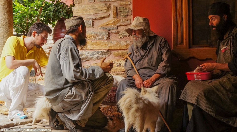 Các tu sĩ trẻ và một công nhân ngồi quanh thầy tu lớn tuổi ngoài tu viện Dochiariou.