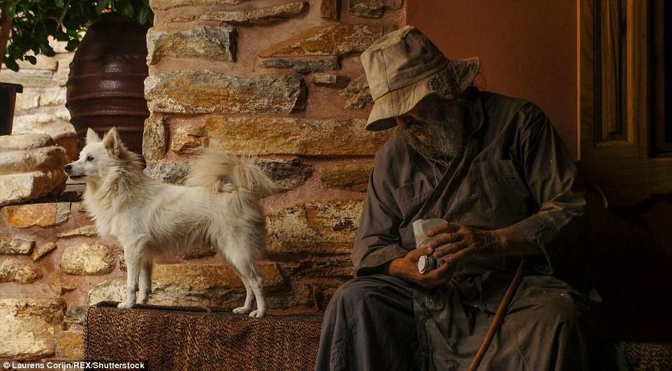 Một thầy tu già ngồi ở cửa vào tu viện Dochiariou cùng chú chó của ông.