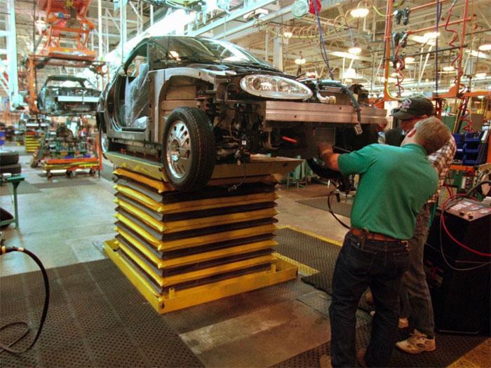 Công nhân tại một nhà máy General Motors lắp động cơ vào điện vào chiếc xe mới trong năm 1996.
