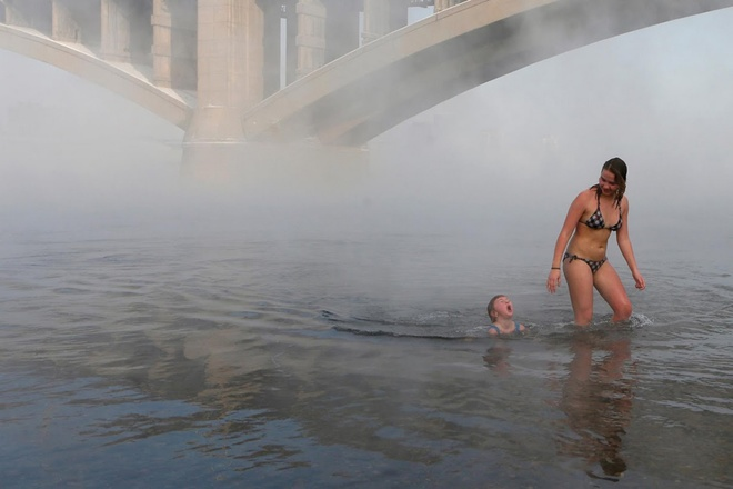 """Nastya Usachyova, 9 tuổi, đang cùng mẹ Natalia, 39 tuổi, khởi động trước khi hòa mình vào dòng sông Yenisei. Mẹ cô bé từng là quán quân môn bơi mùa đông, đã cho con gái mình tham gia môn thể thao có phần mạo hiểm này từ khi bé lên 2 tuổi. Nastya kể lại rằng: """"Lúc đầu cháu cũng thấy lạnh buốt nhưng cháu đã vượt qua được nỗi sợ hãi. Bạn bè cháu cùng nhiều cô chú đều nói rằng bơi lội dưới sông Yenisei vào mùa đông là điều không tưởng. Nhưng có lẽ mọi người đã lầm""""."""