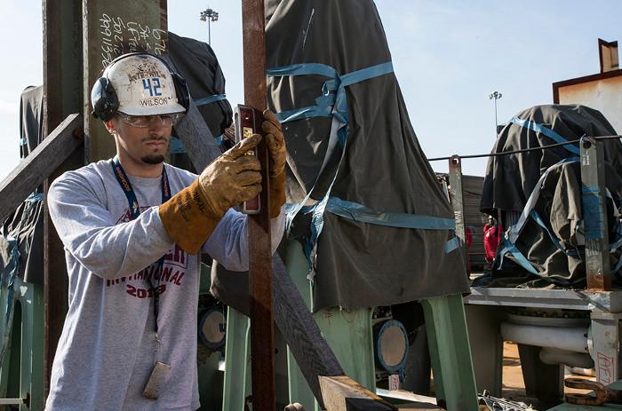 Trong hình là chuyên viên lắp đặt đường ống Trevin Wilson đang làm việc trên tàu USS John F. Kennedy.