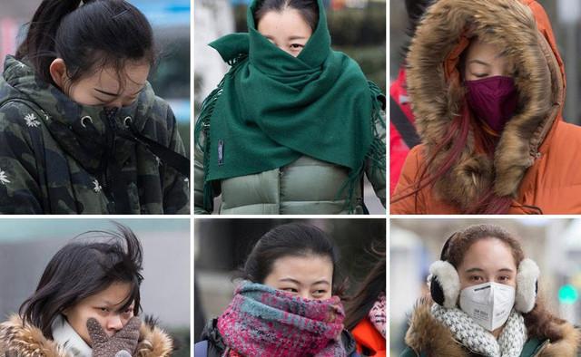 Người dân mặc áo ấm ra đường trong gió lạnh.