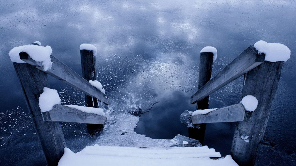 Cầu thang gỗ phủ tuyết bên mặt hồ đã kết băng mỏng.