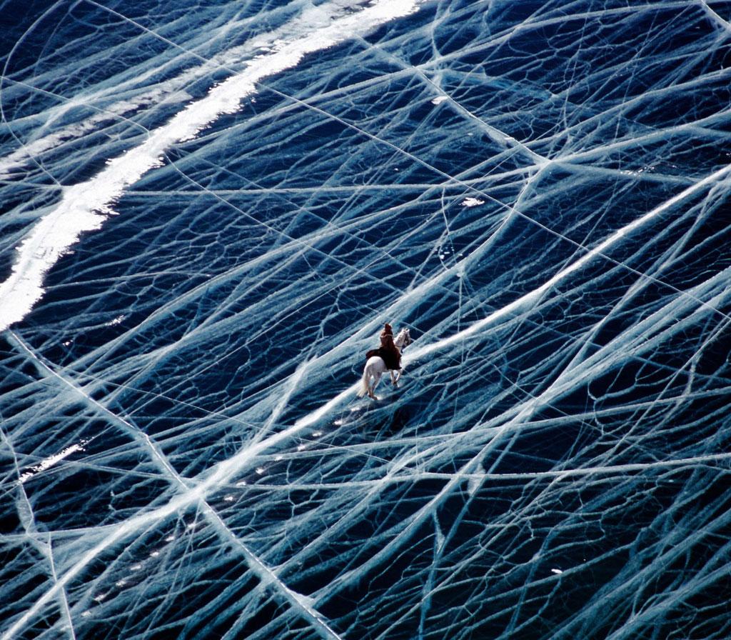 Cưỡi ngựa vượt hồ băng ở vùng Xibia của nước Nga. Mặt hồ chằng chịt những vết nứt ngang dọc như tấm kính vỡ.