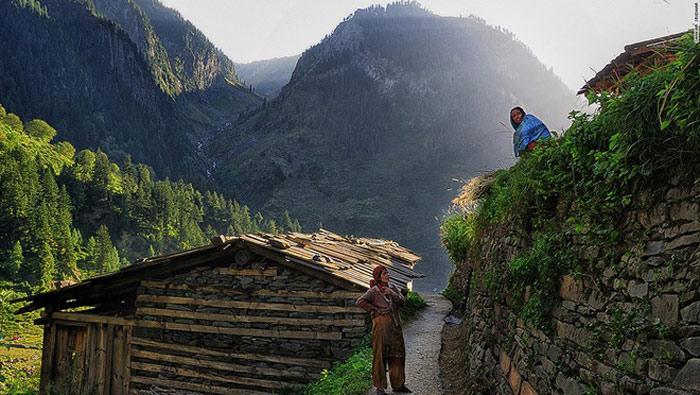 Sự cổ kính của Bara Bangal thể hiện ở khắp mọi nơi, từ những túp nhà, các con đường mòn, cho tới những bức tường được xây bằng đá ôm lấy vách núi. Trong hình là hai người phụ nữ đang trò chuyện qua bờ tường đá và những ngọn núi kia có thể là nơi chồng họ đang đi chăn đàn gia súc.