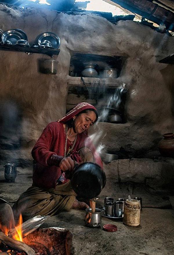 """Bất kể chỗ nào bạn cũng được chào đón bằng những nụ cười, lời mời trà và bữa cơm trưa. Một cụ ông trong làng chia sẻ: """"Đó là truyền thống. Chúng tôi sẽ cảm thấy bị tổn thương khi khách được mời mà không ở lại ăn uống cùng người dân"""". Ông đang rót swig arrack (một loại rượu của Ấn Độ) mời khách uống."""