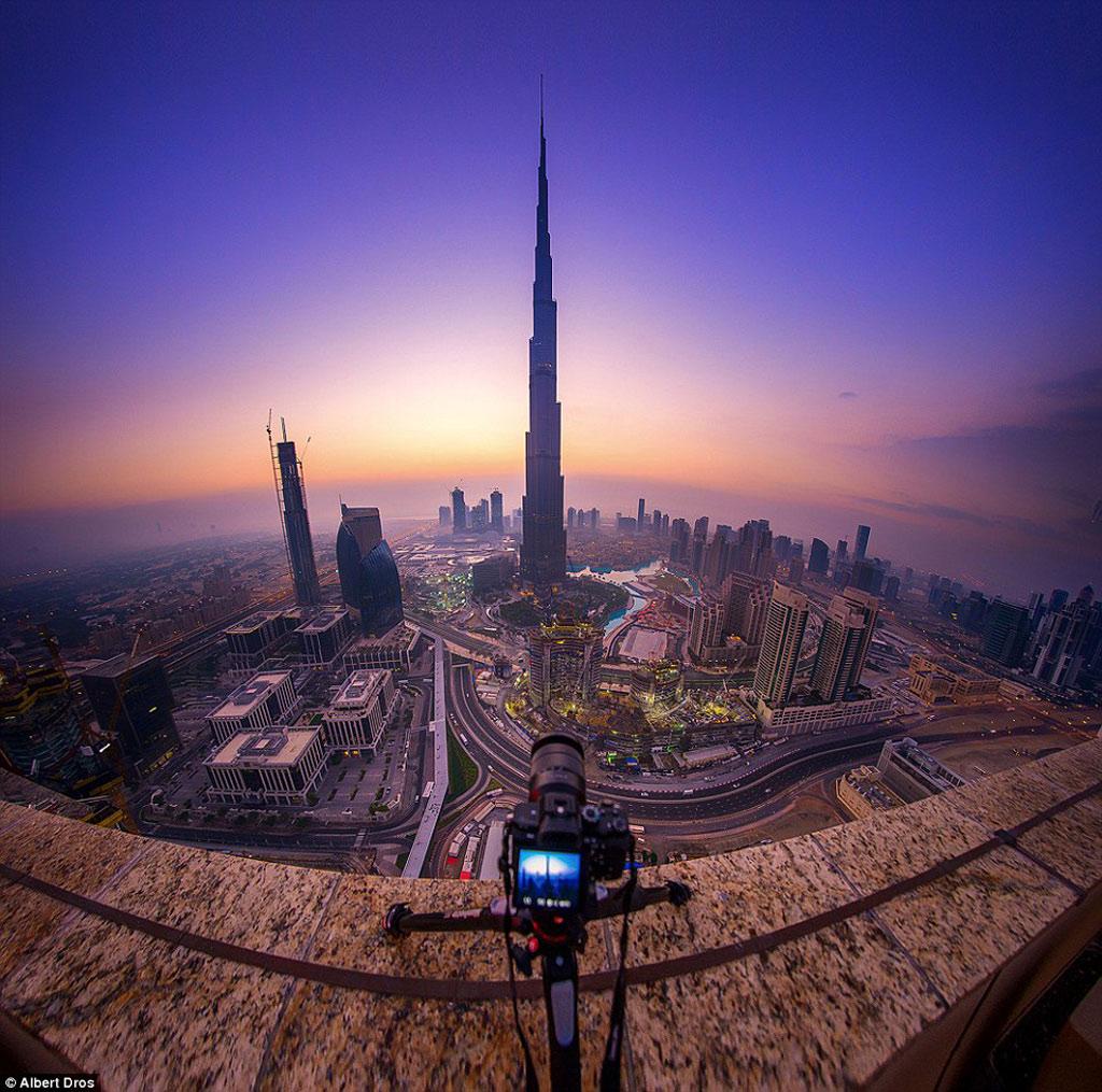 Dưới ánh hoàng hôn, thành phố naTòa tháp Khalifa - công trình cao nhất thế giới (829,8 m) - là trung tâm và một trong những biểu tượng nổi tiếng, thể hiện tham vọng của Dubai.ày vẫn không mất đi vẻ màu nhiệm.