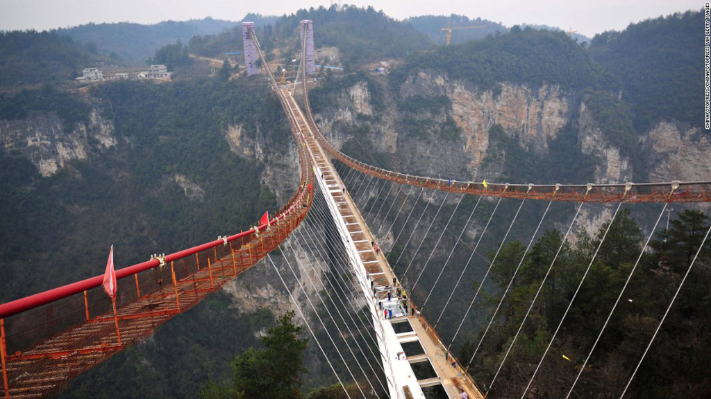 Các công nhân đang lắp đặt các tấm đáy của cây cầu kính dài nhất thế giới. Dự kiến mở cửa vào tháng 5/2016, cầu dài 430 m, rộng 6 m, nằm ở độ cao 300 m trên vực sâu tại Hồ Nam.