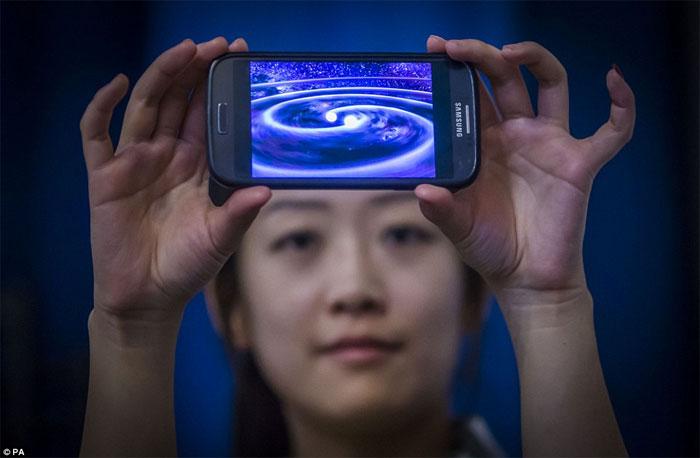 Sinh viên Muzi Li tại Viện Nghiên cứu hấp dẫn tại Đại học Glasgow giữ một điện thoại mà cho thấy một mô phỏng máy tính của sóng trọng lực.