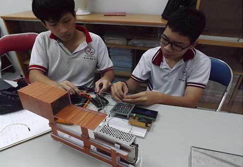 Trần Trung Tiến và Lê Tấn Sang với thiết bị ghi nhận bức xạ hạt nhân.