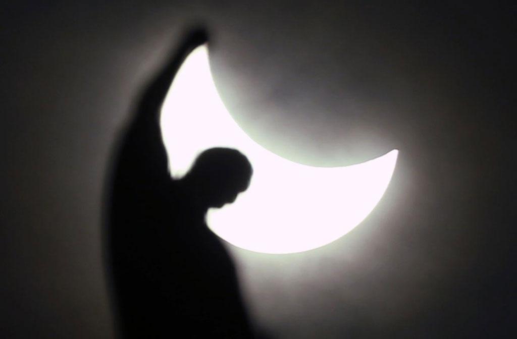 Mặt Trăng xuất hiện và bắt đầu che Mặt Trời khi hiện tượng Nhật thực xảy ra trên một bức tượng ở nhà thờ Gothic Doumo, Milan, Italy