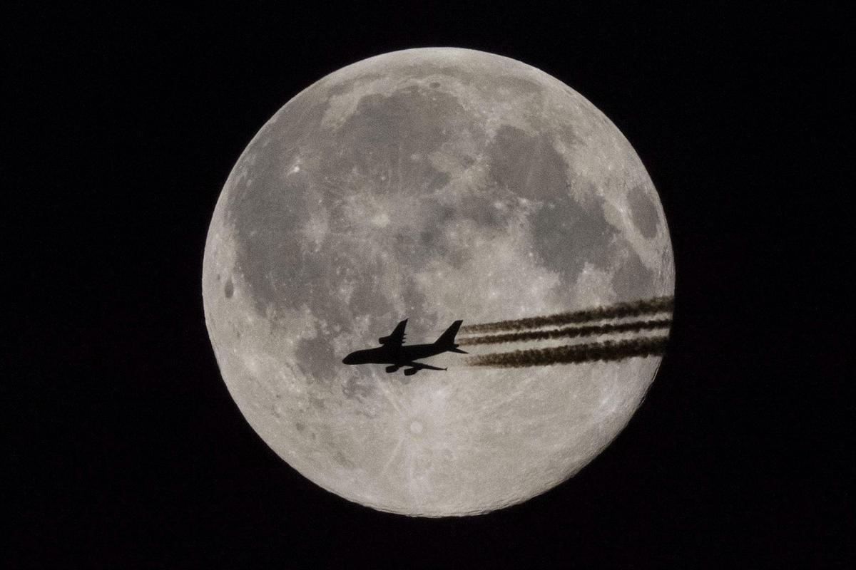 Một chiếc máy bay bay ngang qua Mặt trăng tròn đang chiếu sáng xuống bầu trời đêm ở Teglas, Hungary, 03/06/2015.