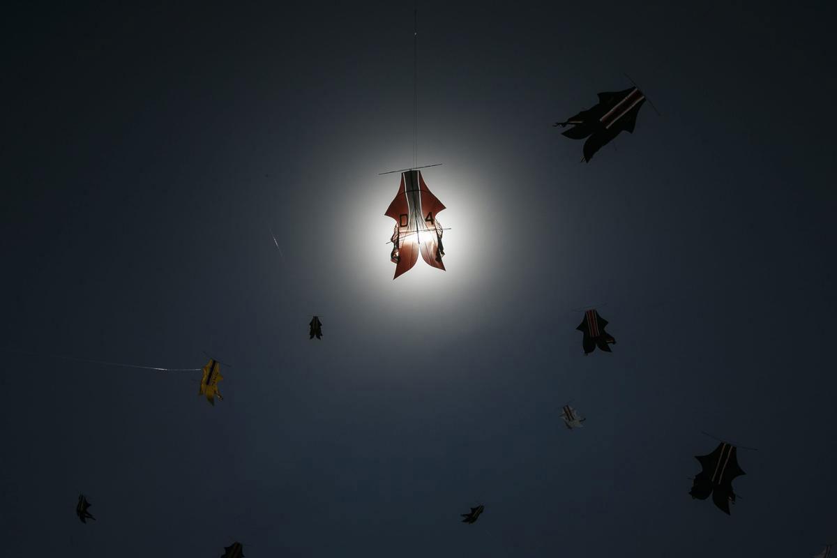 Một con diều bay ngang qua mặt trời khi người dân Bali đang thả diều ở lễ hội Bali Kite Festival, tại Sanur, Bali, Indonesia, 03/07/2015. Màu chính của những con diều truyền thống của người Bali là đen, đỏ, trắng và vàng, tượng trưng cho hiện thân của các vị thần Hindu. Lễ hội này được tổ chức để quảng bá cho du lịch Bali.