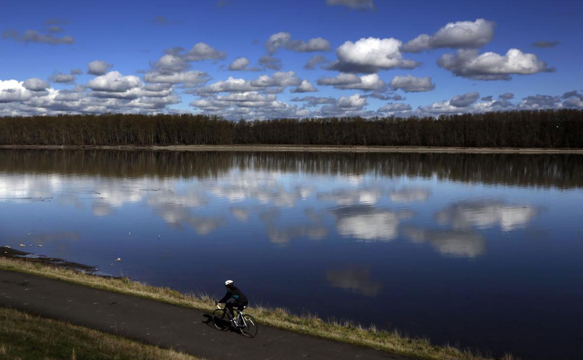Một người đi xe đạp bên con đường ven sông Columbia với bầu trời đầy những gợn mây, in bóng xuống mặt nước, ở Portland, Oregon.