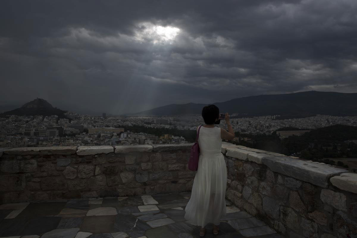 Một cô gái chụp ảnh thành phố Athen khi những đường ray ánh sáng chiếu xuyên