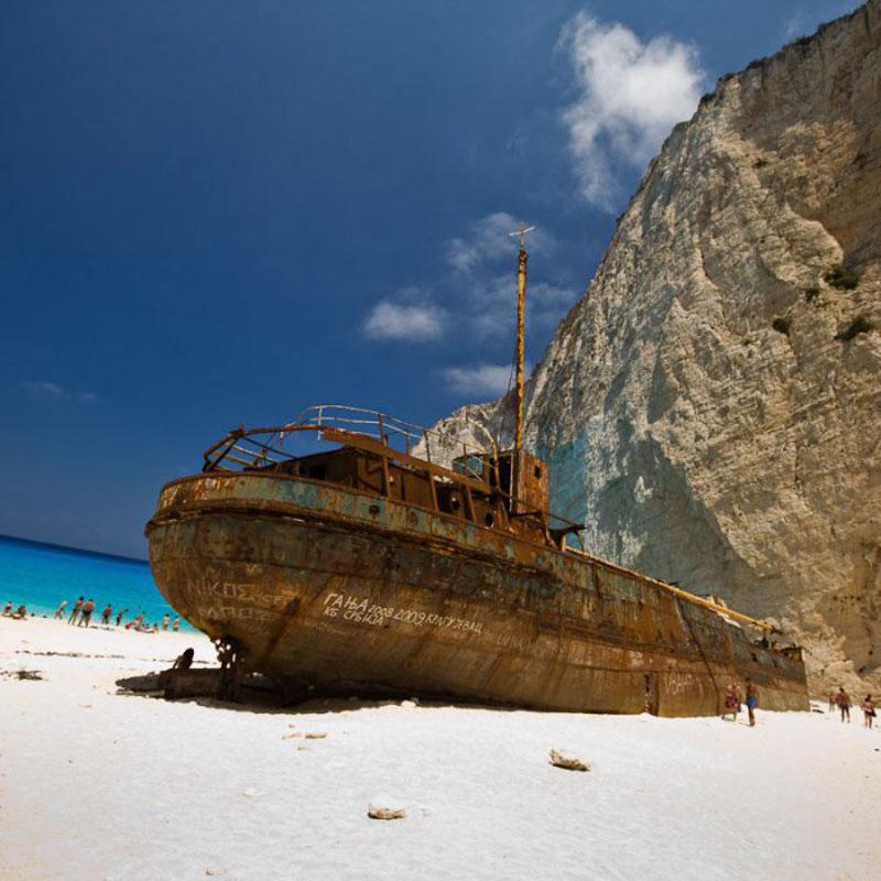 """Navagio có nghĩa là """"đắm tàu"""". Sở dĩ bãi biển có cái tên lạ này là vì một con tàu mang tên MV Panagiotis chở thuốc lá buôn lậu đã bị đắm ở đó vào năm 1983."""