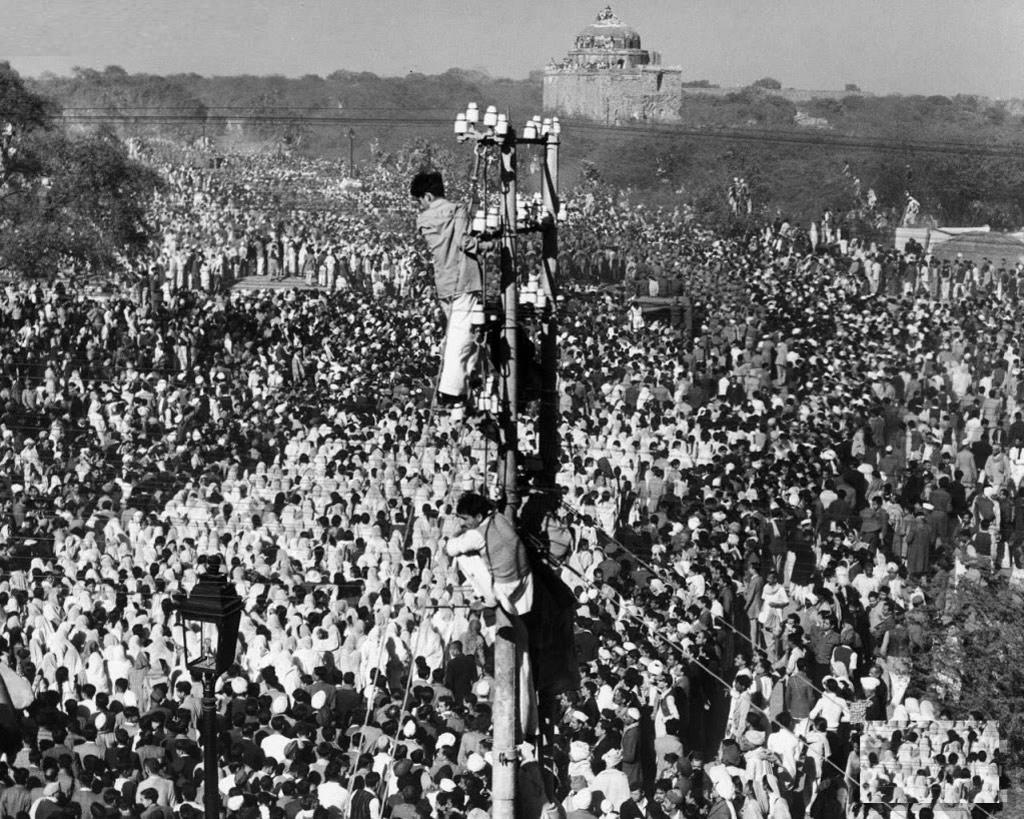Một người đàn ông trèo lên một cột điện để xem những nghi thức cuối cùng của tang lễ Gandhiji