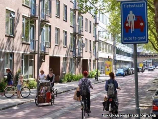 """Tấm biển báo có nghĩa: """"Phố xe đạp: xe hơi chỉ là khách""""."""