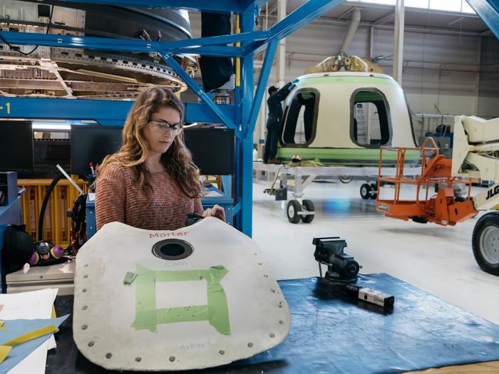 Một kỹ sư đang ráp dù che phủ tàu vũ trụ New Shepard.