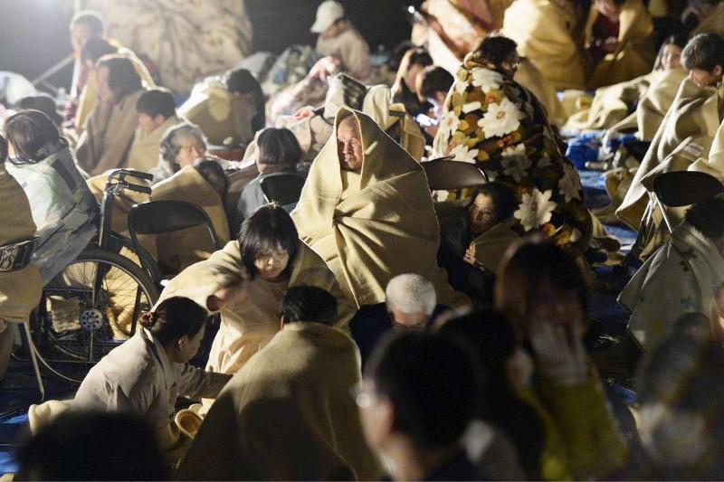 Người dân trú chân bên ngoài một tòa nhà làm việc ở Mashiki, Kumamoto.