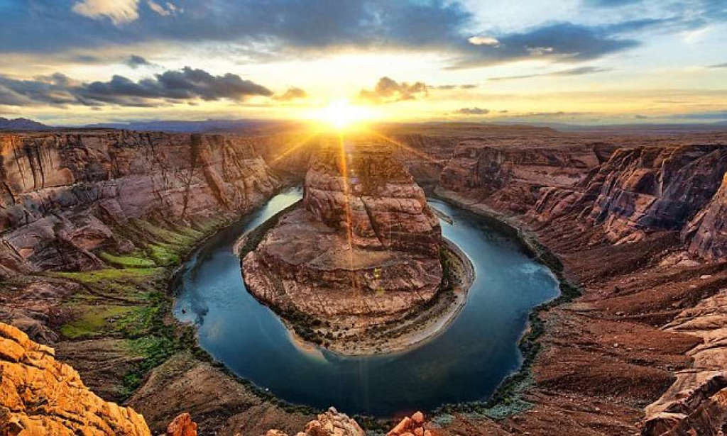 Hồ nước hình móng ngựa độc đáo với ánh mặt trời thấp thoáng trên đất Arizona, Hoa Kỳ.