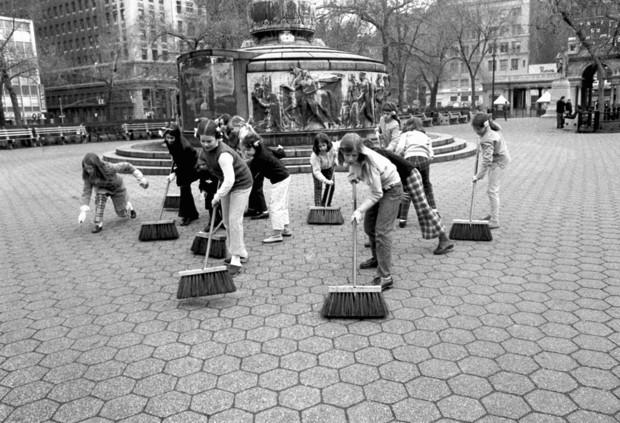 Trong ảnh, các nữ sinh New York quét dọn gần đài tưởng niệm ở công viên Union của thành phố.