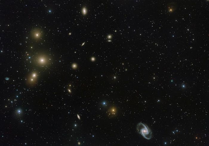 """Bên trái hình là ba đốm sáng thẳng hàng, đốm ở giữa là """"thiên hà ăn thịt"""", phát triển nhờ hấp dẫn và nuốt thiên hà nhỏ hơn."""