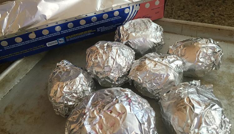 Dùng giấy bạc gói kín quả bơ và đặt nó lên trên khay nướng.