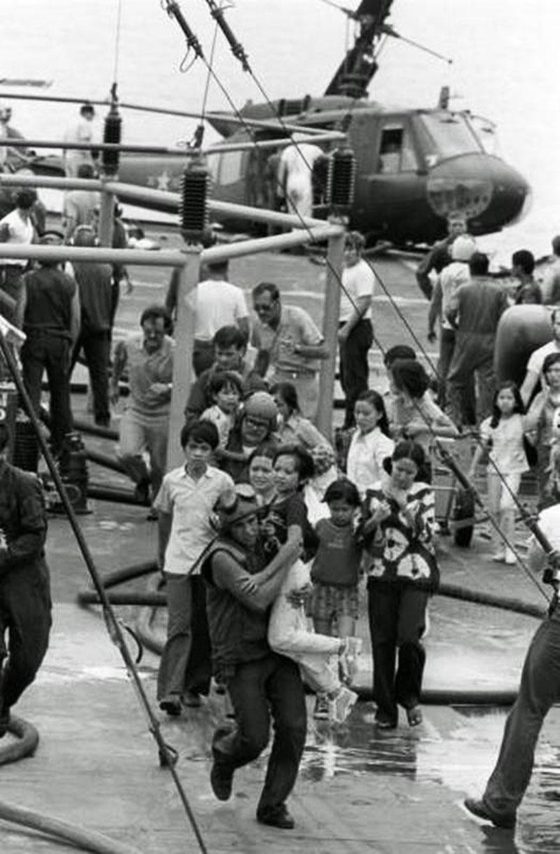 Phi công Mỹ bế một em bé đến nơi trú ẩn an toàn trên chiến hạm USS Blue Ridge sau khi chiếc trực thăng chở em cùng nhiều người khác va chạm trong lúc hạ cánh trên boong tàu.