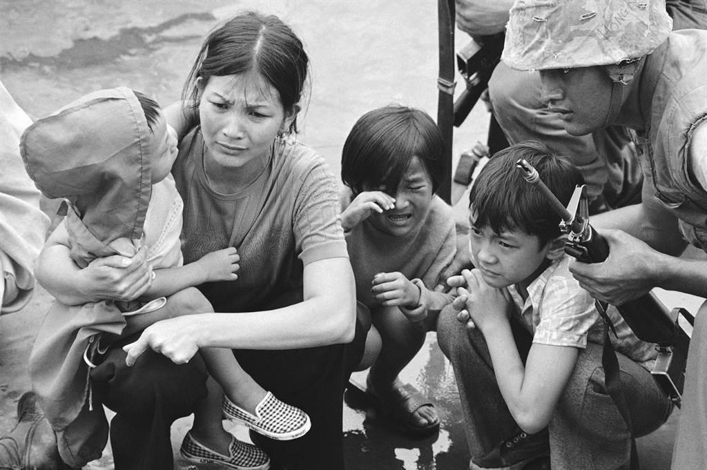 Một phụ nữ cùng ba người con chờ lên trực thăng của lính thủy đánh bộ Mỹ.
