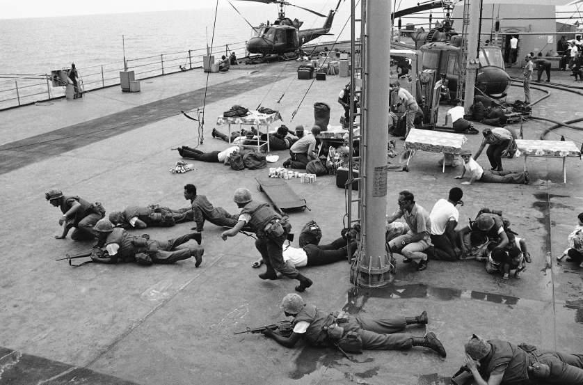 Lính thủy đánh bộ Mỹ nằm rạp trên boong chiến hạm USS Blue Ridge để tránh những mảnh vỡ kim loại văng ra từ một máy bay trực thăng khi nó hạ cánh và va chạm với một chiếc trực thăng khác.
