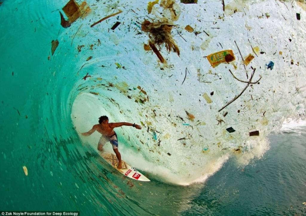 Vận động viên lướt ván Indonesia Dede Surinaya đang lướt giữa rác rưởi tại đảo Java, hòn đảo thu hút nhiều khách du lịch nhất thế giới.