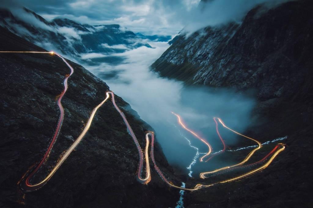 Cảnh tượng ô tô di chuyển dọc con đường uốn lượn trong khi sương dần tan trên thung lũng Trollstigen, Na Uy