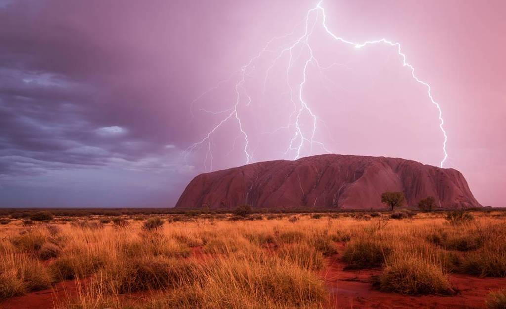 Những tia sét chùm đánh trúng cấu trúc đá Uluru khi giông bão quét qua khu vực Yulara, Northern Territory, Australia.