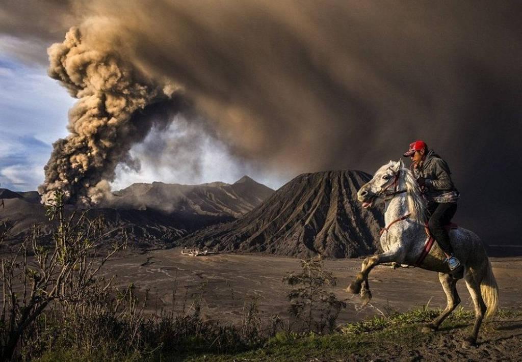 Du khách cưỡi ngựa gần núi lửa Bromo đang phun trào tro bụi tại Probolinggo, Đông Java, Indonesia.