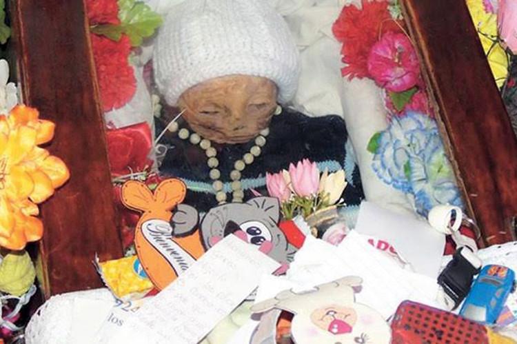 Xác ướp bé Gaitan bên cạnh hoa và đồ chơi của những người đến viếng.